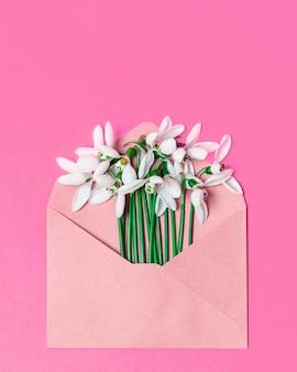 Envelope de papel ofício aberto com flores da flor da primavera em uma superfície rosa. camada plana, vista superior.
