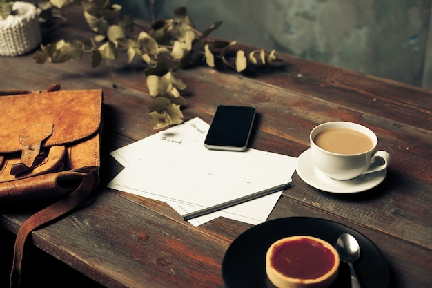 Envelope de papel ofício aberto, folhas de outono e café na mesa de madeira