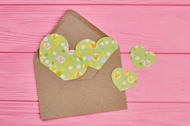Envelope de papel ofício com corações de papel. corações de papel artesanal verde sobre fundo rosa de madeira. feliz dia dos namorados.
