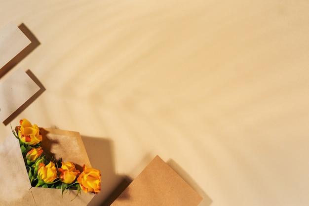 Envelope de papel ofício com rosas amarelas em fundo bege