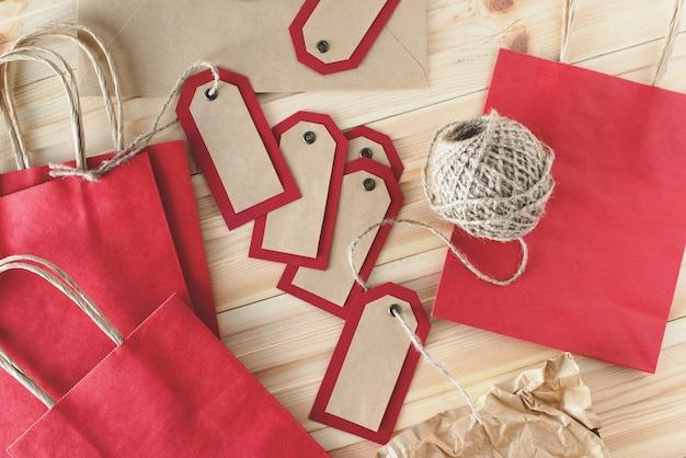 Envelope de papel reciclado, saco de papel vermelho e etiquetas no fundo da mesa de madeira vintage