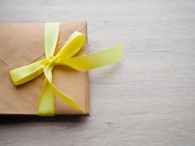 Envelope de presente no chão de madeira, envelope de presente caseiro