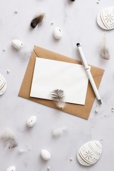 Envelope de vista superior com caneta rodeada por ovos de páscoa