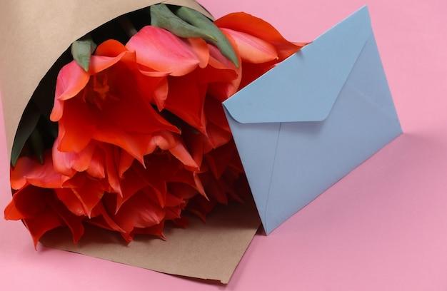 Envelope e buquê de tulipas vermelhas em fundo rosa. aniversário, dia dos namorados ou proposta de casamento.