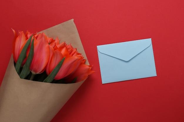 Envelope e buquê de tulipas vermelhas em fundo vermelho. aniversário, dia dos namorados ou proposta de casamento. vista do topo