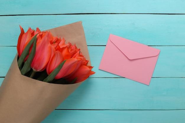 Envelope e buquê de tulipas vermelhas sobre fundo azul de madeira. aniversário, dia dos namorados ou proposta de casamento. vista do topo