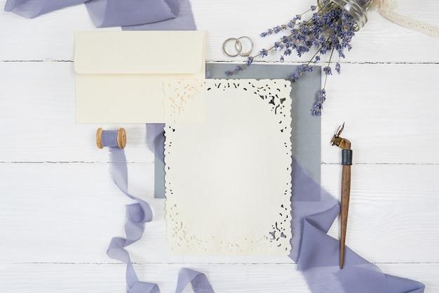 Envelope e fita com dois anéis de casamento com flores de lavanda e caneta caligráfica