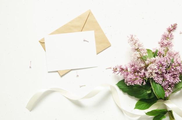 Envelope e flores lilás. flores da primavera. vista superior, plana leigos. copie o espaço.