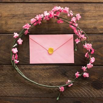 Envelope e galhos com flores em forma de círculo