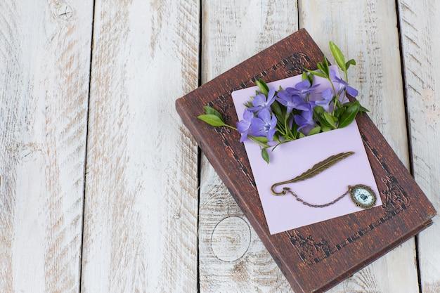 Envelope e nele são flores roxas, um livro e um marcador para um livro