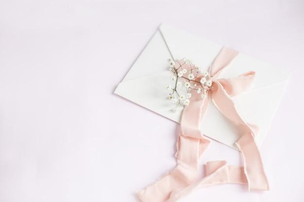 Envelope em um fundo branco-rosa com fita de seda pêssego e flores cor de rosa. convite de casamento. cartão do dia das mães. lugar para texto. copie o espaço.
