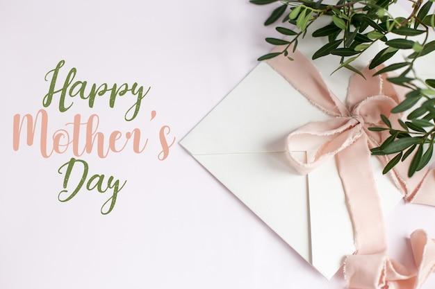 Envelope em um fundo branco-rosa com fita de seda pêssego, galho verde e flores. cartão do dia das mães.