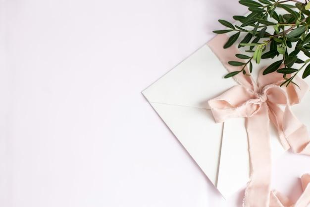 Envelope em um fundo branco-rosa com fita de seda pêssego, galho verde e flores. convite de casamento. cartão do dia das mães. lugar para texto. copie o espaço.