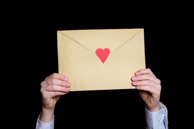 Envelope grande com um coração vermelho nas mãos das crianças. fechar-se.