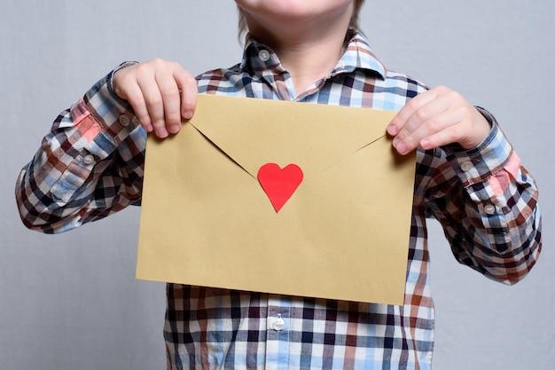 Envelope grande com um coração vermelho nas mãos das crianças.
