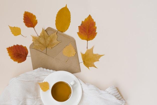 Envelope kraft com folhas de outono amarelo, uma xícara de porcelana branca com chá preto e uma manta branca de malha em um fundo bege, vista superior. copyspace. hogge, outono deitado.
