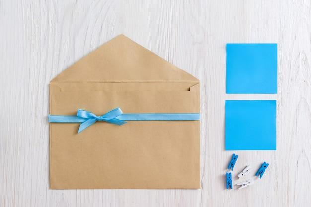 Envelope marrom com fita azul e adesivos em madeira branca