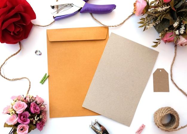 Envelope marrom e cartão marrom em branco com buquê de flores sobre fundo branco