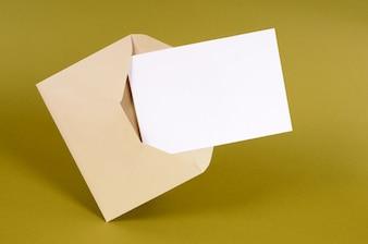 Envelope marrom liso com cartão de mensagem em branco