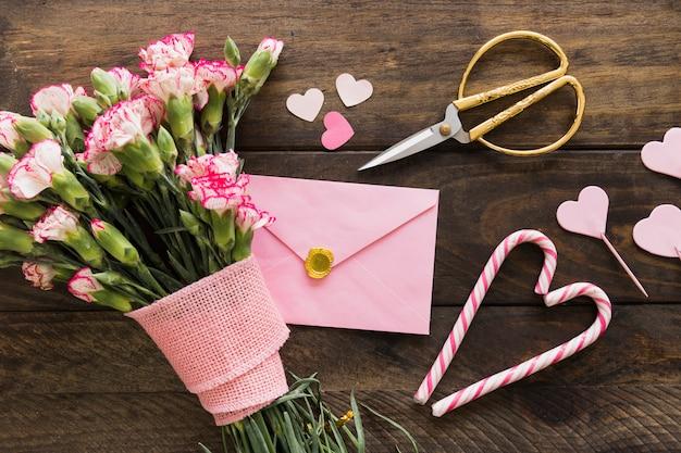 Envelope perto de buquê de flores com fita, tesoura e bastões de doces