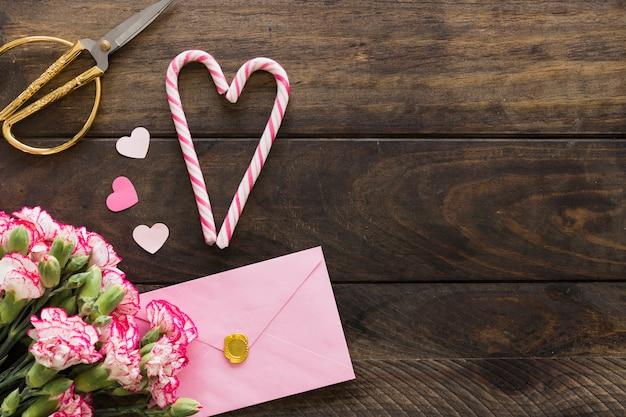 Envelope perto de buquê de flores, tesouras e bastões de doces