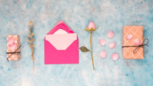 Envelope perto de caixas de presentes, flores e pétalas