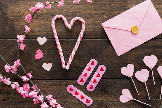 Envelope perto de galhos com flores e bastões de doces