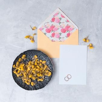 Envelope perto de papel branco e conjunto de flores secas