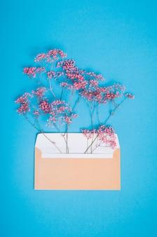 Envelope postal aberto bege com flores de gipsófila rosa dentro