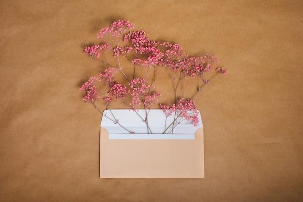 Envelope postal aberto com flores rosa dentro