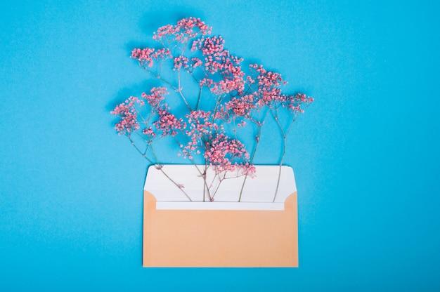 Envelope postal bege aberto com flores rosa