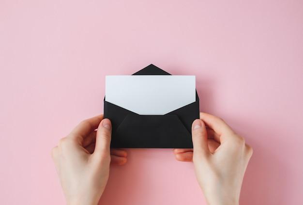 Envelope preto com papel branco em branco em mãos femininas