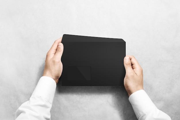 Envelope preto em branco segurando na mão