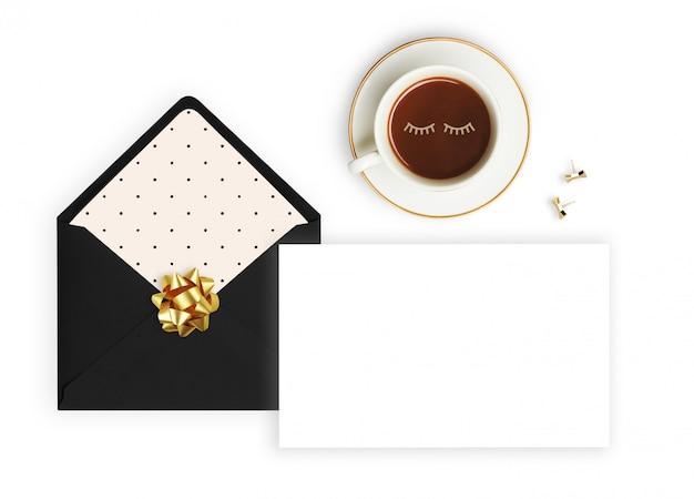 Envelope preto, xícara de café e lápis.
