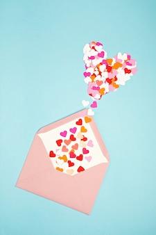 Envelope rosa com confetes em forma de coração, sobre o fundo azul.
