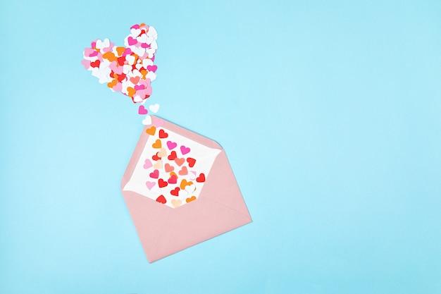 Envelope rosa com confetes em forma de coração