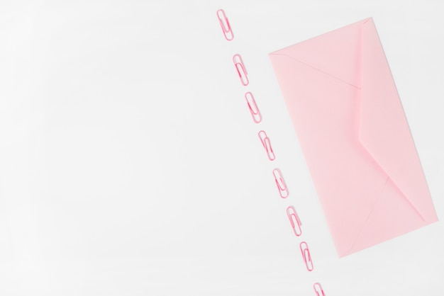 Envelope rosa e clipes de papel no fundo branco