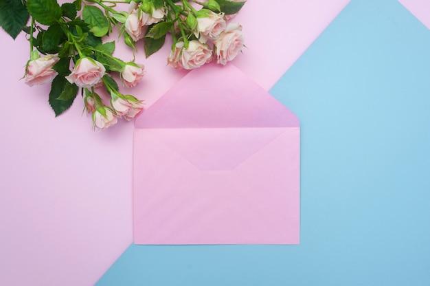 Envelope rosa vazio e botões de rosas cor de rosa