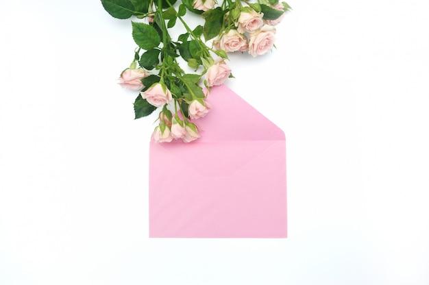 Envelope rosa vazio e botões de rosas