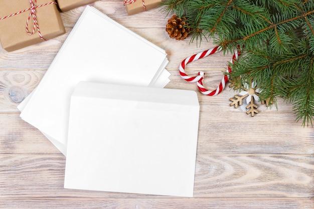 Envelope vazio com a lista de desejos para o papai noel deitado em uma mesa de madeira