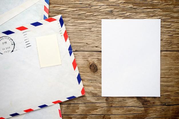 Envelope velho e folha de papel na madeira