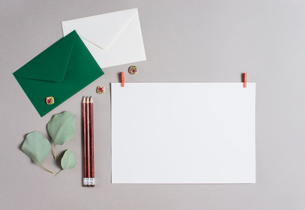 Envelope verde e branco; lápis e papel em branco no pano de fundo cinzento