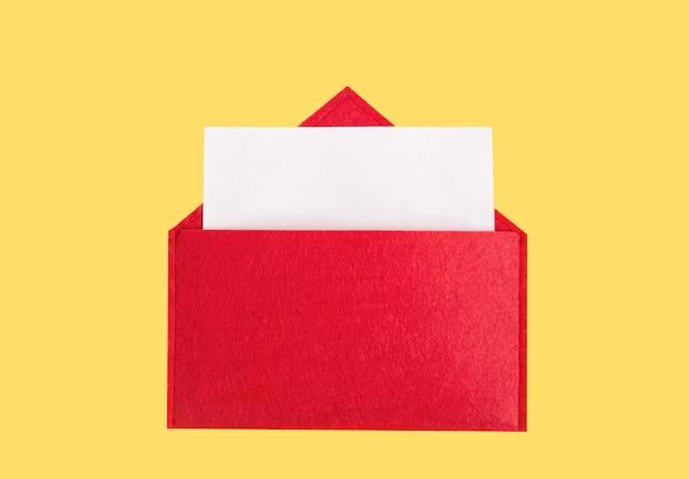 Envelope vermelho aberto com uma folha de papel com mock-up em um fundo amarelo com copyspace.