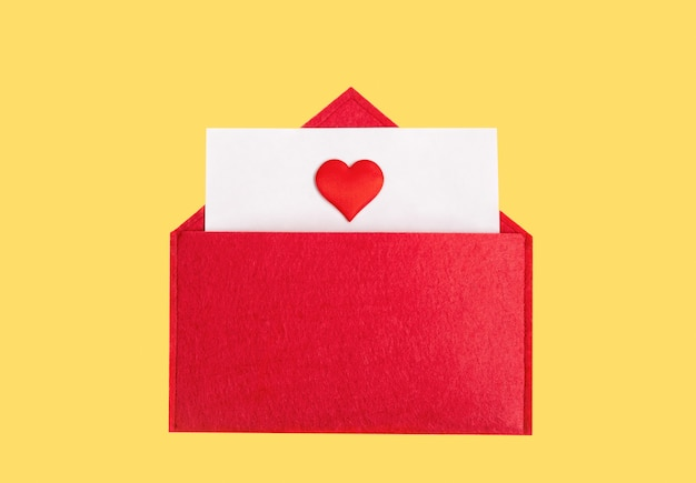 Envelope vermelho aberto com uma folha de papel com um coração em um fundo amarelo com copyspace. conceito de férias do dia dos namorados e notas de amor