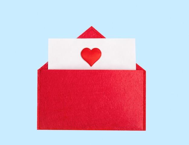 Envelope vermelho aberto com uma folha de papel com um coração em um fundo azul com copyspace. conceito de feriados do dia dos namorados e notas de amor