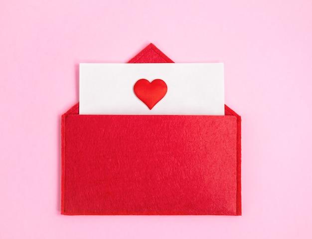 Envelope vermelho aberto com uma folha de papel com um coração em um fundo rosa com copyspace. conceito de feriados do dia dos namorados e notas de amor, cartas de natal e ano novo para o papai noel