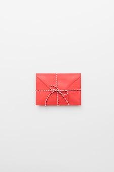 Envelope vermelho amarrado na mesa