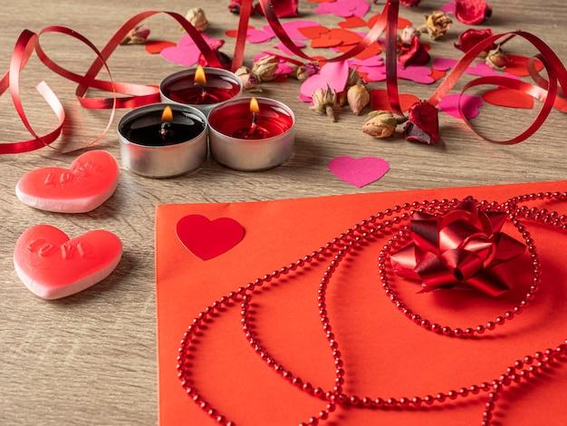 Envelope vermelho ao lado de velas com pétalas de rosa vermelhas e fita na mesa