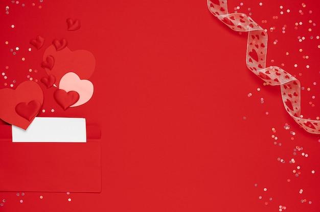 Envelope vermelho com carta de amor em fundo vermelho com muitos corações ao redor. corações jorram do envelope. corações voam para fora do envelope. carta de amor