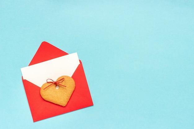 Envelope vermelho com cartão branco em branco para texto e coração em forma de biscoitos de gengibre sobre fundo azul.